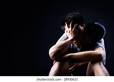 A man is sad and being consoled/embraced by his partner