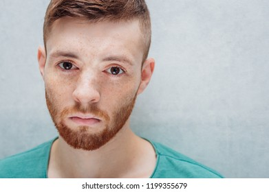 Man with a sad facial expression on a gray background close-up