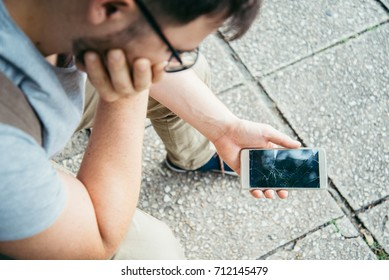 man with sad look holding smartphone with cracked screen