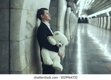 Man is sad with a teddy bear toy in his hands. The concept of his beloved woman did not come to the meeting.