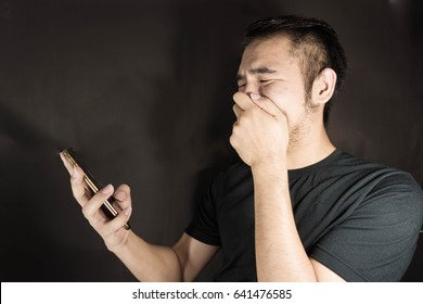 Man sad, when he is seeing the phone in dark background.