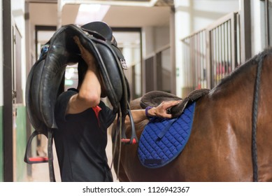 Man saddle a horse in the stall.