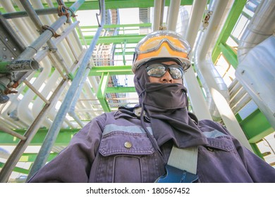 Man with safety personal protection equipment in industrial plant background