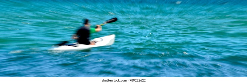 A man sailing with kayak into sea water (lenses zoom effect)