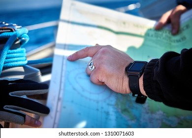 A man sailor on a sailing yacht studying the map. hands close up