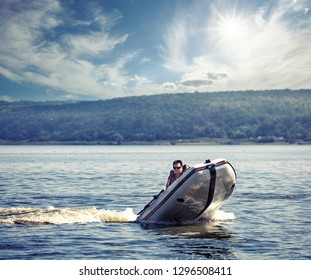 Man sails on a fast motorboat. A man in sunglasses drives an inflatable motorboat at high speed. Sunny summer landscape. The concept of freedom of speed and travel