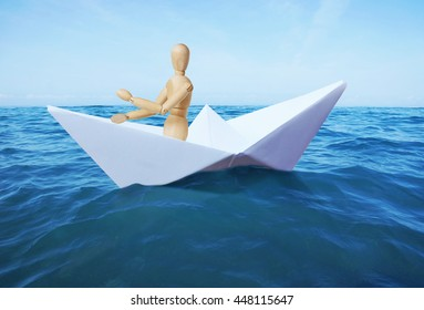 Man sails on the sea in a toy paper ship