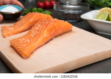 Man salting steak from salmon fish on wooden cutting board. Side view on food ingredients.