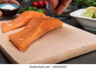 Man salting steak from salmon fish. Side view on food ingredients.