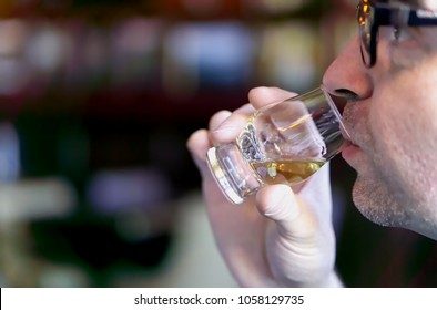 Mann, der Whisky aus einem Whisky-Degustationsglas probiert, Nahaufnahme.