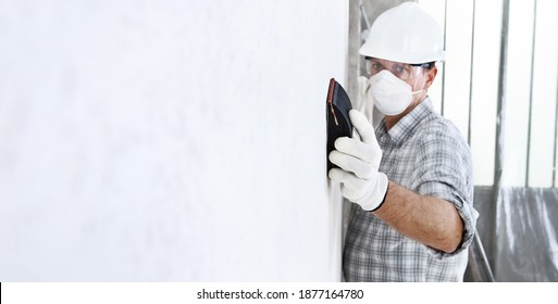 Mann Sand die Wand mit Sandpapier, professioneller Bauarbeiter mit Maske, sicheren harten Hut, Handschuhe und Schutzbrille. Innengebäude, Kopienraum-Hintergrund