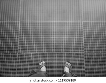 Man in sandals standing on metal grid background