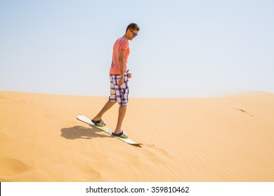 Man sandboarding down the dune in a desert