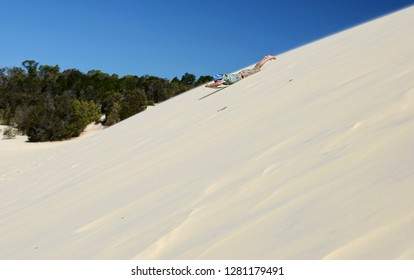 Man sandboarding in the dunes, Cairns, Australia. Man sandboarding in the desert - extreme desert activity. Summer activities. Leisure. Sport. Movement