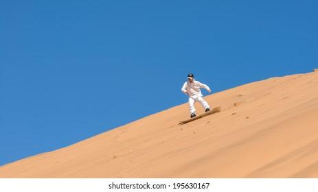 Man sandboarding in Namibia, Africa
