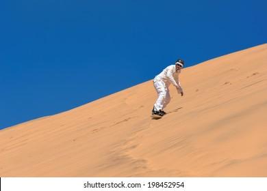 Man sand-boarding in Swakopmund, Namibia