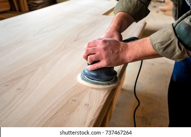Man sanding wood with orbital sander in a workshop