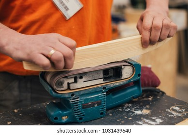 Man sanding a wood with  sander in a workshop