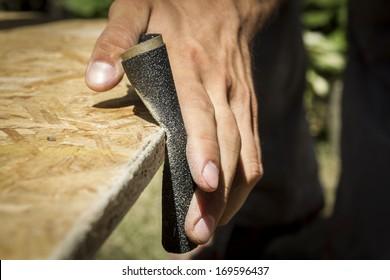 Man sanding wooden panel.