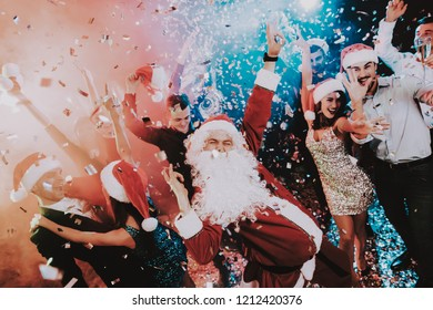Man in Santa Claus Costume on New Year Party. Happy New Year. People Have Fun. Indoor Party. Celebrating of New Year. Young Women in Dresses. Young Men in Suits. Happy People. Man with White Beard.