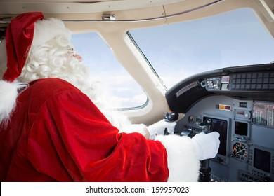 Man in Santa costume holding control wheel in cockpit of private jet