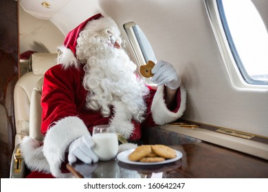 Man in Santa costume holding cookie while looking through private jet's window