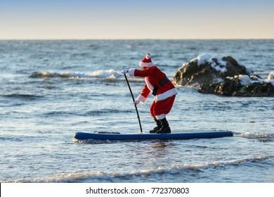 Man in Santa costume with SUP board on winter sea