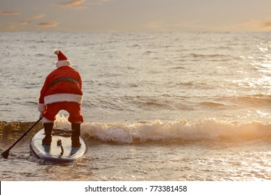 Man in Santa costume with SUP board on winter sea