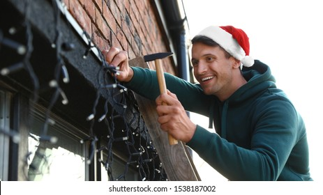 Man in Santa hat decorating house with Christmas lights outdoors