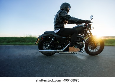 Man sat on motorcycle on the road during sunset. Chopper high power motorcycle goes over landscape.