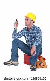 Man sat on tool box sending text message
