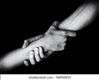 Man saving, rescuing and helping woman by holding or griping the forearm. Male hand and arm pulling up female. Concept of rescue, love, friendship, support, teamwork, partnership, reaching, couple