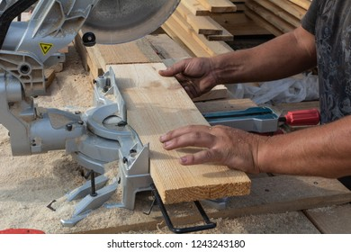 Man sawing a wood board with a circular saw