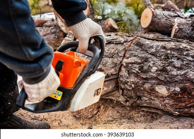 Man sawing wood chainsaw.