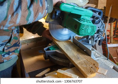 The man is sawing the wooden plank with the green electrical circular mitre saw.