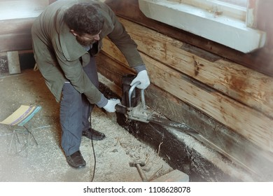 a man saws an electric saw with a lower beam in a wooden house