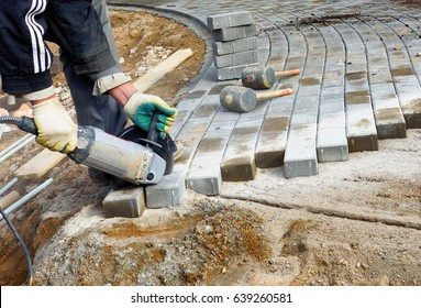 A man saws an electric saw with a paving slab, repairing a stone path.