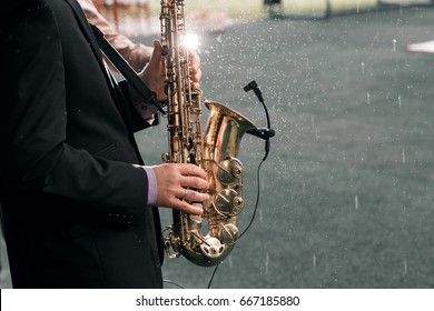 Man with a saxophone stands under rain