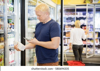 Man Scanning Bar Code On Product Through Mobile Phone