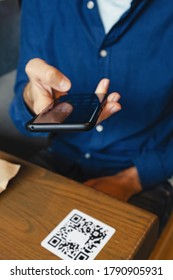 Man scanning the QR code with mobile phone for order foods at the restaurant.