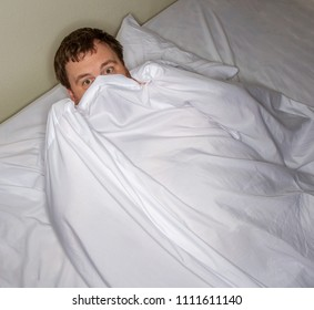 Man scared of something and he is hiding under the covers