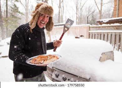 A man in a scarf and fur hat goes out in the snow to light his barbecue while the thermostat reads a chilling minus 10 degrees.  Good concept for being tired of winter and ready for a sunny vacation.