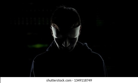 Man in scary mask isolated on dark background, serial killer hiding identity