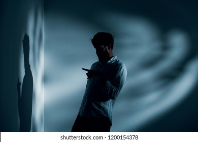 Man with schizophrenia standing alone in dark interior talking to his shadow, photo with copy space on the wall