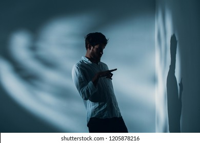 Man with schizophrenia standing alone in a room pointing at his shadow on the wall, real photo with copy space