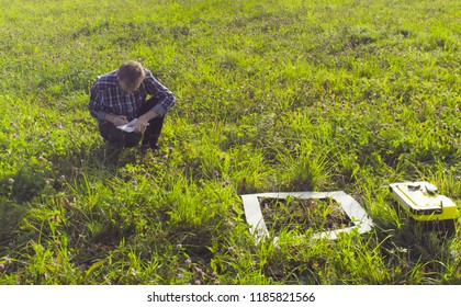 The man scientist ecologist sitting on the meadow and making notes in the diary. Field work