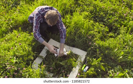 The man scientist ecologist sitting on the meadow and measuring the height of a plant. Field work
