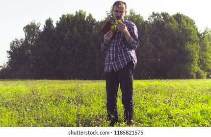 The man scientist ecologist standing on the meadow and examining plant. Field work