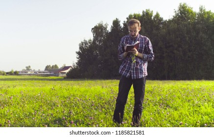 The man scientist ecologist standing on the meadow and making notes in the diary. Field work