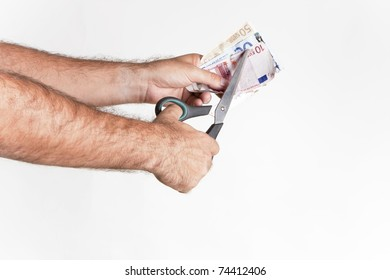 a man with scissors cutting a euro banknote